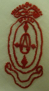 The embroidered oval is topped by the king's crown and there is an empty decorative scroll beneath. Total height is just over two inches by just over one in ch wide.